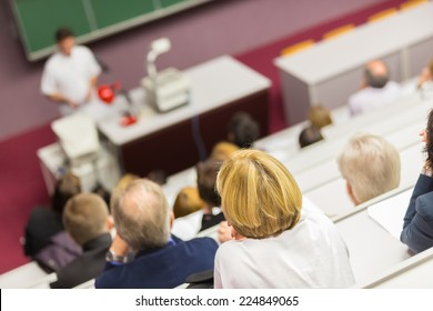 Lecturer at university. Healthcare expert giving a talk to medical faculty professors. Participants listening to lecture and making notes.
