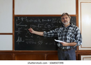 Lecturer at the university leads the lesson,  formulas on the blackboard
