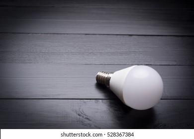 Led bulb green technology on dark wooden background