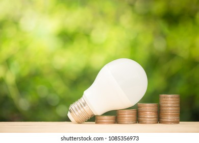 LED bulb on the growing coin stack with green nature background on warm light tone for saving energy concept