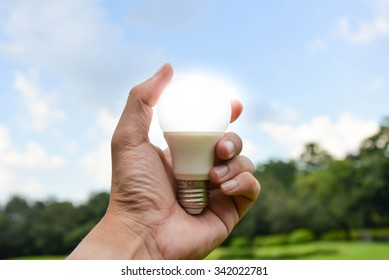 LED Bulb on hand with nature background