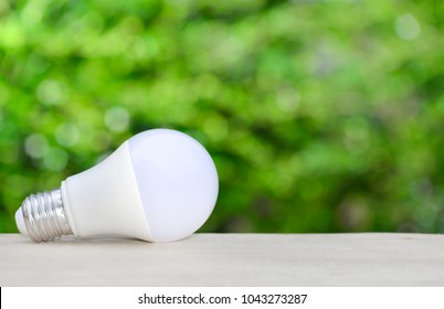 LED bulb on the wooden table with green nature background for eco saving concept