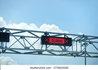 LED closed sign at country border gate against blue sky. Border closed during coronavirus pandemic lockdown to restrict non-essential travel. Canada extending travel restrictions with United States.