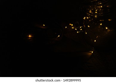 LED fairy string warm small tiny lights spilling out of a container and across a table on a black background
