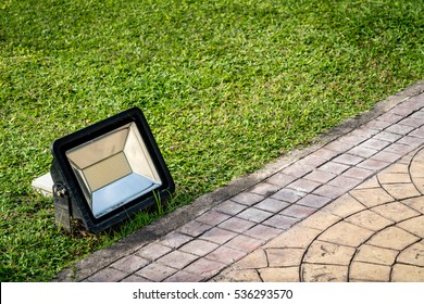 LED Flood light, Spot light lantern on green grass with concrete sidewalk