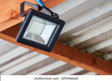 LED flood light, spot light on the top of the roof. Powerful construction lighting floodlight a lantern for illumination of a local area at night