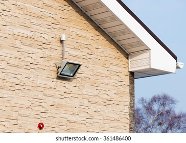 LED floodlight on wall of house covered with lite brown decorative slate stone surface.