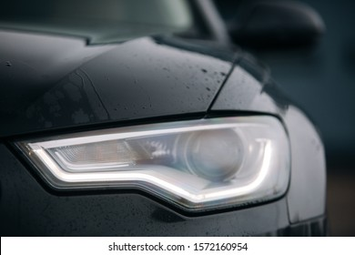 Led headlight of modern car at the rainy day