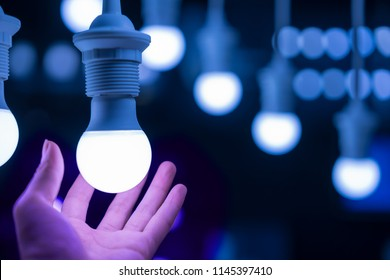 LED lamps and hand blue light science technology background