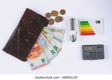 Led Light Bulb and european coins and  banknotes sticking out of the wallet (isolated). Calculator and efficency rating label.