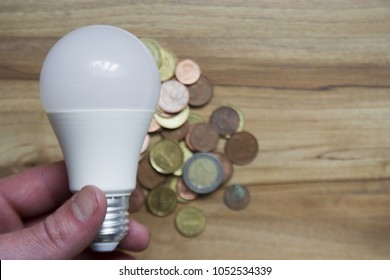 Led light bulb in a hand. bulb on wooden table background and a pile of euro coins.