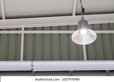 led light bulb in the industrial lamp is bright on the ceiling of the new warehouse with copy space, High Bay Lighting.