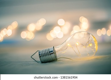 LED light bulb is lying in the bed. Symbol for ideas and innovation. Spot lights in the blurry background.