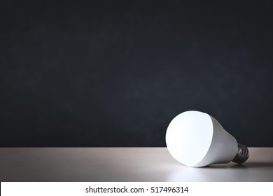 LED light bulb on table with black background