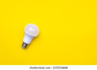 LED light bulb on yellow background with copy space