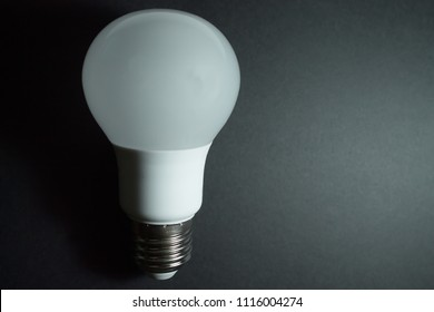 LED light bulb, used in light fixtures that produces light using light-emitting diode, placed on a dark background leaving free space on the right.