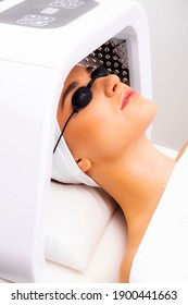 LED light therapy lamp. Facial phototherapy procedure in the salon. Skin restoration and treatment at home.