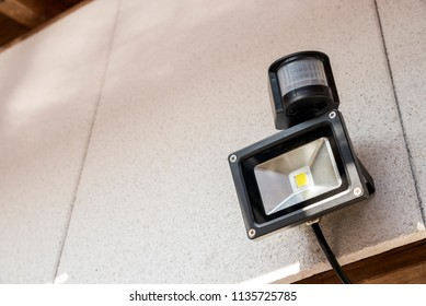 LED motion sensor light attached to outer white wall