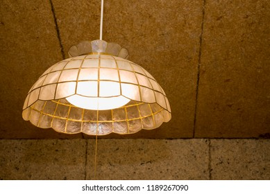 LED pendant light emitting warm color in front of fibrous coating wall