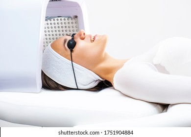 Led phototherapy for the face. Phototherapy in cosmetology. A beautiful young woman in a suit and glasses lies in the cosmetologist's office on the face phototherapy procedure.