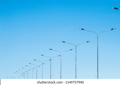 LED road lighting. Road lighting poles. A lot of road lanterns against the blue sky. Metal poles with lamps. Road construction.