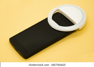 LED selfie circular ring light lamp on smartphone on pastel yellow background. Clip-on flash light camera phone for taking selfie photos. Compact device for bloggers and vloggers. Selective focus