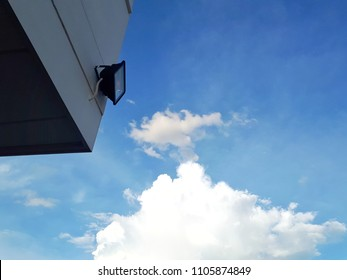 LED spotlight installed on the corner of wall of white building for security and safety with blue sky background