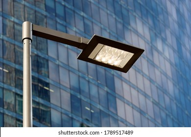 LED street lamp post glowing on skyscraper background. Modern led lights in city, saving of electrical energy