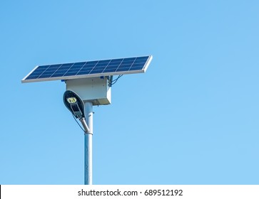 LED street light with solar cell on clear sky, closeup view.
