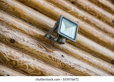 LED street lights fixed on a wooden log house wall