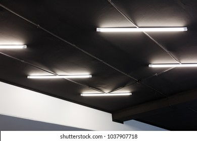 Led tube lights on black office ceiling. Minimal loft design