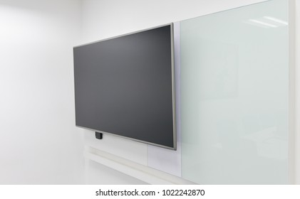 LED TV installed to the white wall of the meeting room with white board