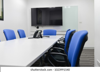 LED TV installed to the white wall of the meeting room with black ip phone on the table