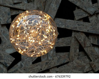 LED wire string light in glass ball with wooden background, selective focus.