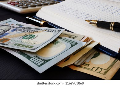 Ledger, calculator and dollar banknotes. Bookkeeping.