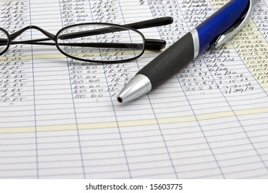 ledger with pen and glasses