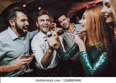 Ledy in Green. Duet. Trendy Nightclub. Have Fun. Dress. Background. Cheerful. Smile. Smiling Girl.Singing Songs. Handsome Men. Beautiful Girls. Friends at Karaoke Club. Karaoke Club. Celebration.