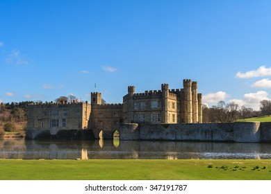 Leeds Castle from across moat with embankment in foreground.