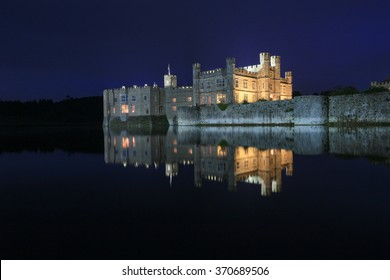 Leeds Castle, Kent, England, at night, reflected in the moat.