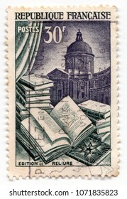 Leeds, England - April 18 2018: An old french postage stamp showing an open book with illustration and a library in the background