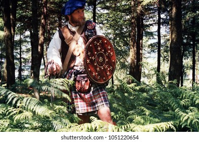 Leeds England July 1998. An unidentified reenactor wears the period clothing of a Scottish Jacobite rebel he stands proudly  sword in hand in a wood at a reenactment of the Battle of Culloden 1745.