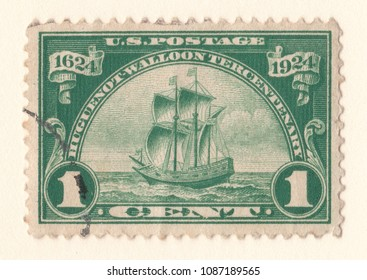 Leeds, England - May 6 2018: an old green American postage stamp with an image of a sailing ship celebrating the hugenot walloon centenary of 1924