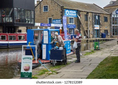 LEEDS AND LIVERPOOL CANAL. SKIPTON, NORTH YORKSHIRE, UK. 31st MAY 2018. Customers queue to buy at an Ice Cream selling barge on the Leeds and Liverpool canal at Skipton.