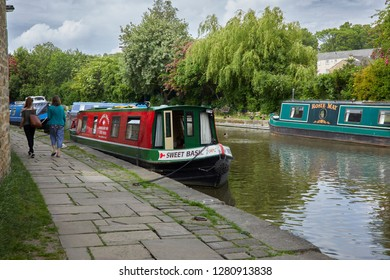 LEEDS AND LIVERPOOL CANAL. SKIPTON, NORTH YORKSHIRE, UK. 31st MAY 2018. A bright day and two adult females walk on the tow path with colourful holiday barges moored alongside