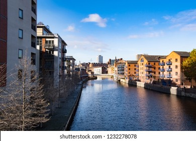 Leeds riverside, West Yorkshire, United Kingdom - November 13th 2018: Autumn sunshine lights up the converted warehouses on the redeveloped waterfront at Leeds city centre.