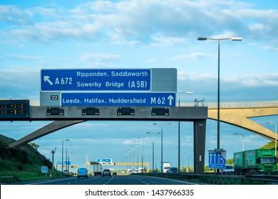 Leeds, UK - 19th June 2019: A Blue British motorway sign above the motorway directing transport towards Leeds, Huddersfield, Halifax, M62, Ripponden, Saddleworth and Sowerby Bridge.