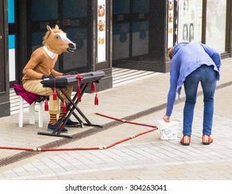 LEEDS, UK - 24 July 2015.  Man with a horses head playing the keyboard and busking for money.  Lady putting money into busker, begger, performer's hat