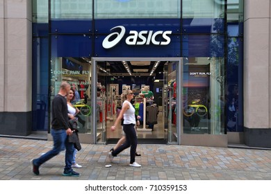 LEEDS, UK - JULY 12, 2016: People walk by Asics store in Leeds, UK. Asics is a Japanese sportswear and footwear producer since 1949.