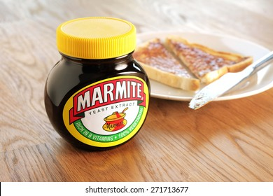 Leeds, United Kingdom - April 22nd, 2015: Jar of Marmite. Slice of toast on a white plate in background. Marmite is a food paste, made from yeast extract and has a distinctive salty flavor.