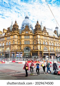 Leeds, West Yorkshire, England - August 20 2021: An exterior shot of Leeds Kirkgate market with several people crossing the road in the foreground